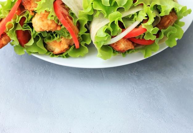 Doner kebab sur une assiette blanche. shawarma avec viande, oignons, salade et tomate sur fond gris. Photo Premium