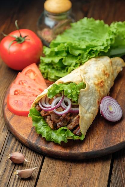 Doner kebab est allongé sur la planche à découper. shawarma avec viande, oignons, salade est allongé sur une vieille table en bois blanche. Photo Premium