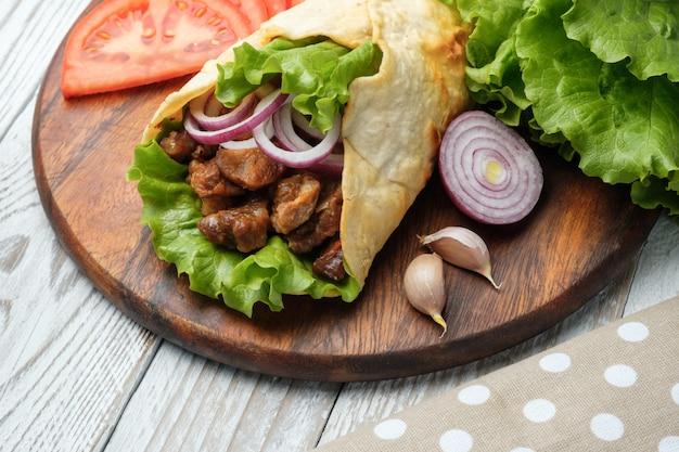 Doner kebab est allongé sur la planche à découper. shawarma avec viande, oignons, salade repose sur une vieille table en bois sombre. Photo Premium