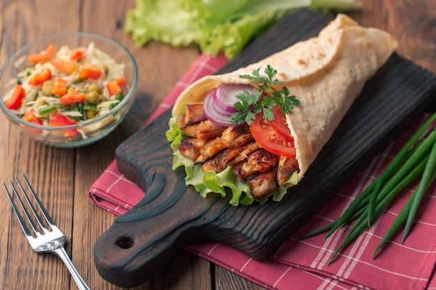 Doner kebab est allongé sur la planche à découper. shawarma avec de la viande de poulet, des oignons, de la salade repose sur une vieille table en bois sombre. Photo Premium
