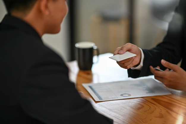 Donner une carte d'appel vierge au visiteur closeup shot avec conversation d'affaires. Photo Premium
