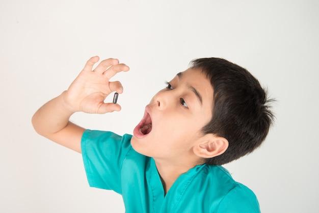 Donner des médicaments aux enfants, un garçon essaie d'avaler des médicaments en comprimés Photo Premium