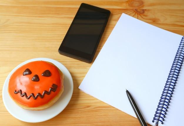 Donut halloween jack o lantern avec smartphone et cahier à reliure à anneaux sur un bureau en bois Photo Premium