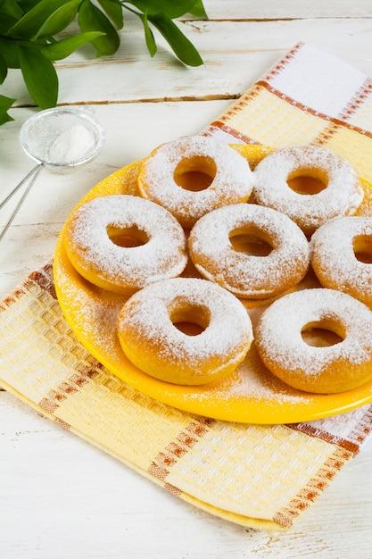 Donuts en poudre de sucre en poudre sur une plaque jaune Photo Premium