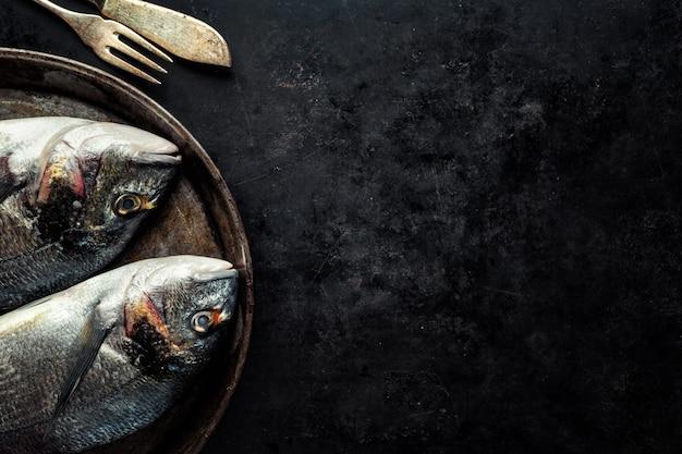 Dorado poisson avec des ingrédients sur dark Photo gratuit