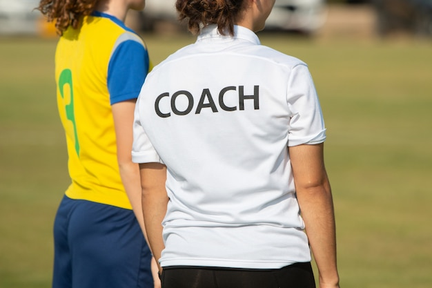 Dos de l'entraîneur sportif portant la chemise coach sur un terrain de sport en plein air Photo Premium