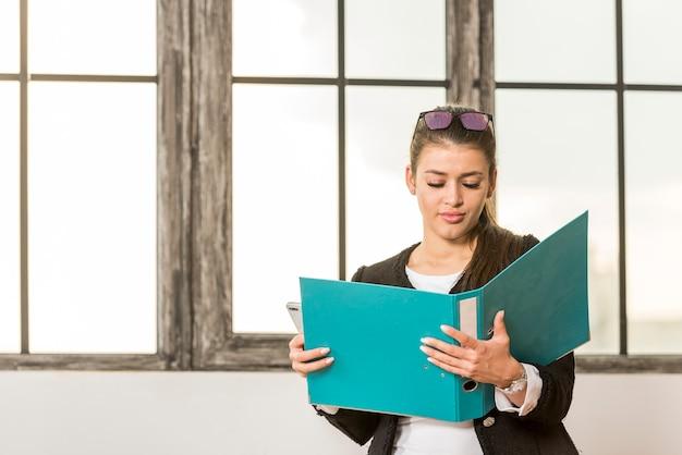 Dossier de lecture de femme d'affaires brune Photo gratuit