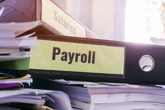 Dossiers de paie et salaires empilés avec étiquette sur classeur noir sur rapport de synthèse des documents Photo Premium