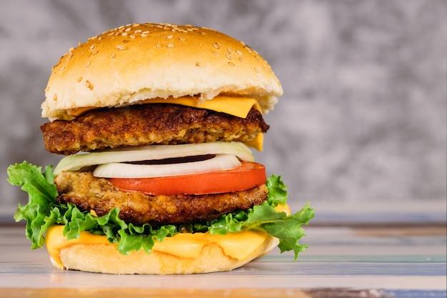 Double burger juteux avec des légumes sur la table. Photo Premium