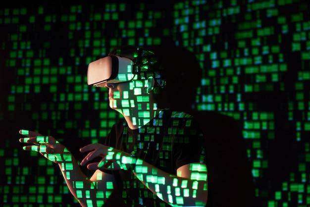 La Double Exposition D'un Homme Caucasien Et D'un Casque De Réalité Virtuelle Vr Est Vraisemblablement Un Joueur Ou Un Pirate Informatique Déchiffrant Le Code Dans Un Réseau Ou Un Serveur Sécurisé, Avec Des Lignes De Code En Vert Photo gratuit