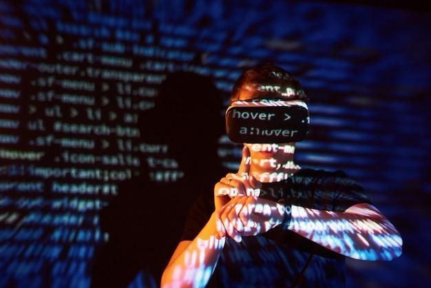 La Double Exposition D'un Homme Caucasien Et D'un Casque De Réalité Virtuelle Vr Est Vraisemblablement Un Joueur Ou Un Pirate Informatique Déchiffrant Le Code Dans Un Réseau Ou Un Serveur Sécurisé, Avec Des Lignes De Code Photo gratuit