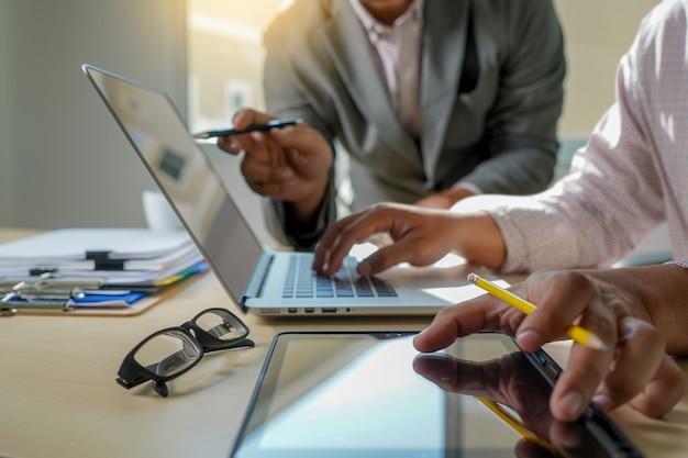 Double exposition de la main de l'homme d'affaires travaillant sur un ordinateur portable sur un bureau en bois avec diagramme de réseau de médias sociaux Photo Premium