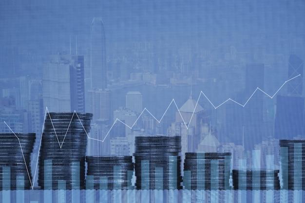 Double exposition pile de pièces avec fond de ville graphique financier Photo Premium