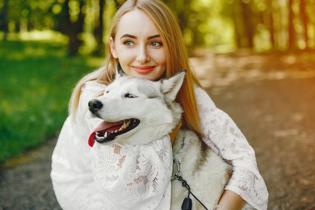 Douce fille aux cheveux clairs vêtue de robe blanche joue avec son chien Photo gratuit