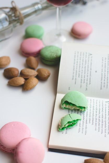 Douce pause avec des macarons et livre Photo gratuit
