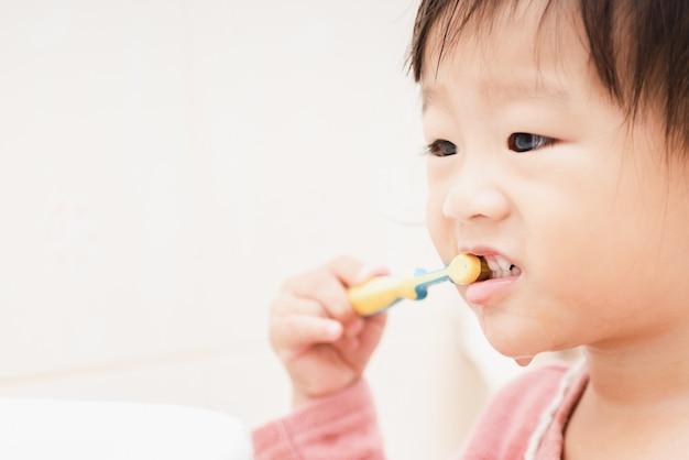Douce Petite Fille Asiatique Se Brosser Les Dents Dans La Salle De Bain Photo Premium