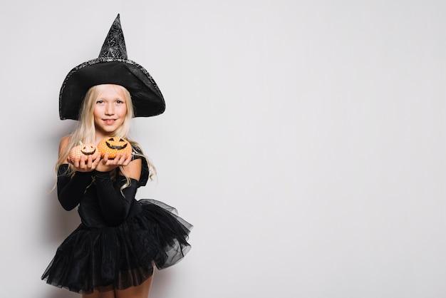 Douce sorcière montrant des citrouilles Photo gratuit