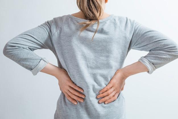 Douleur dans les reins. les femmes se tiennent la main dans le dos. Photo Premium