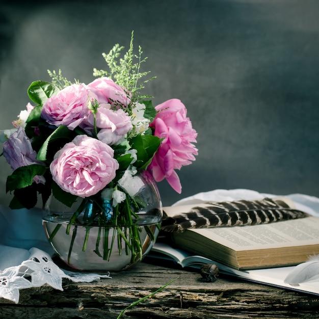 Doux bouquet de roses roses avec des vieux livres sur un vieux bois. Photo Premium