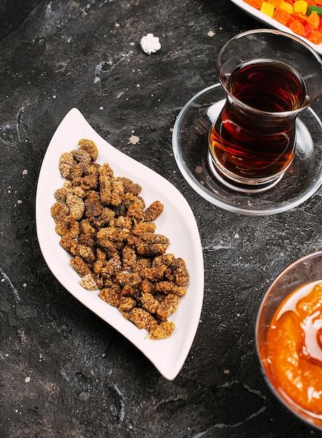 Doux petits bonbons susam dans une assiette blanche avec confiture de pêche et thé turc. Photo gratuit