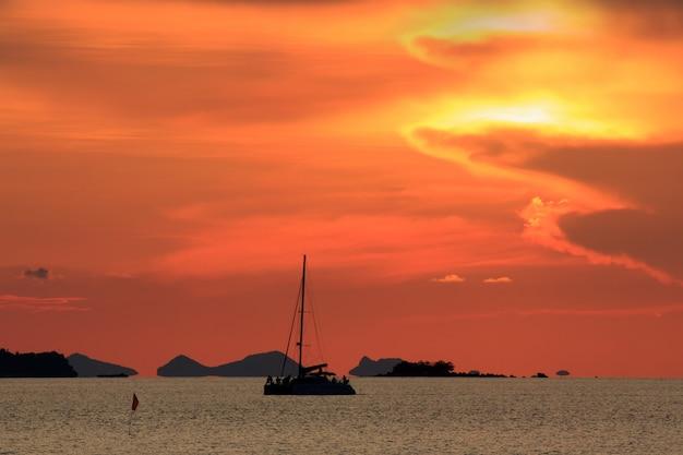 Dramatique ciel coucher de soleil rouge et mer tropicale avec yatch Photo Premium