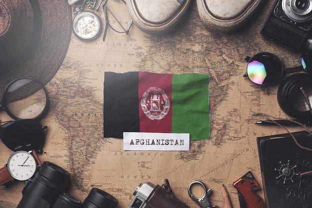 Drapeau De L'afghanistan Entre Les Accessoires Du Voyageur Sur L'ancienne Carte Vintage. Tir Aérien Photo Premium