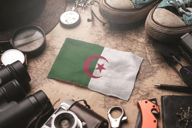 Drapeau De L'algérie Entre Les Accessoires Du Voyageur Sur L'ancienne Carte Vintage. Concept De Destination Touristique. Photo Premium