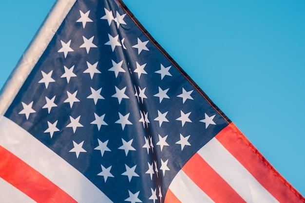 Drapeau américain dans un ciel bleu, gros plan symbole de la fête de l'indépendance, le 4 juillet aux états-unis Photo Premium