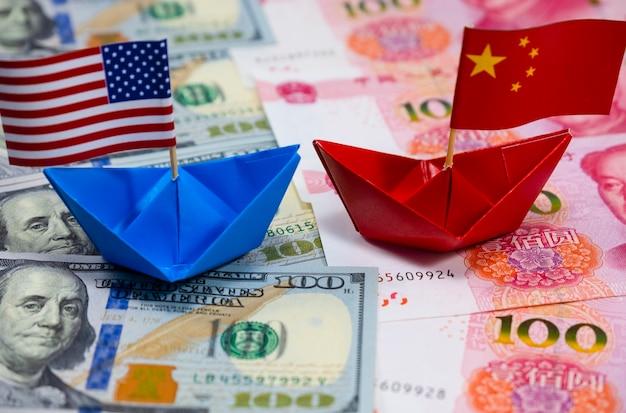 Drapeau américain sur le navire bleu et drapeau de la chine sur le navire rouge avec un fond blanc du commerce de guerre Photo Premium