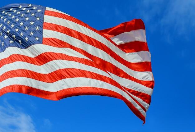 Drapeau Américain Rouge, Blanc Et Bleu Avec Des étoiles Et Des Bandes Dans Le Ciel Bleu Du Vent Photo Premium