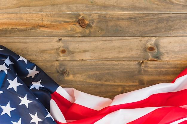 Drapeau américain en tissu sur une surface en bois Photo gratuit