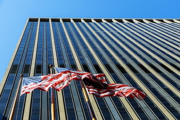 Drapeau Américain, Vent, Contre, Bâtiment Commercial, à, Fenêtres, Et, Ciel Bleu Photo Premium