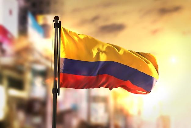 Drapeau de la colombie contre la ville contexte flou au lever de soleil Photo Premium