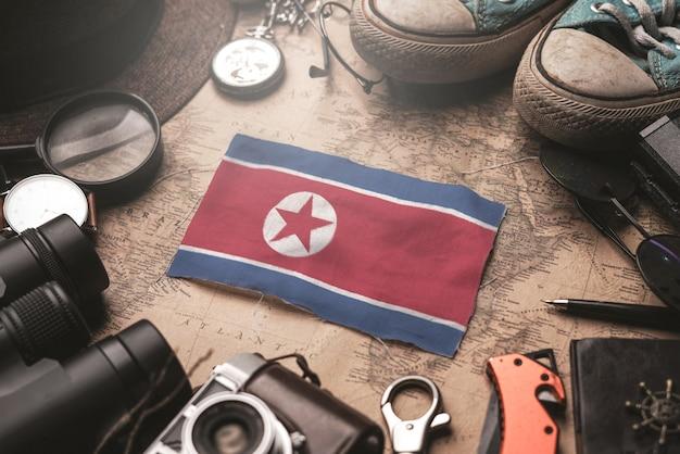 Drapeau De La Corée Du Nord Entre Les Accessoires Du Voyageur Sur L'ancienne Carte Vintage. Concept De Destination Touristique. Photo Premium