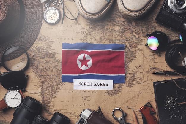 Drapeau De La Corée Du Nord Entre Les Accessoires Du Voyageur Sur L'ancienne Carte Vintage. Tir Aérien Photo Premium