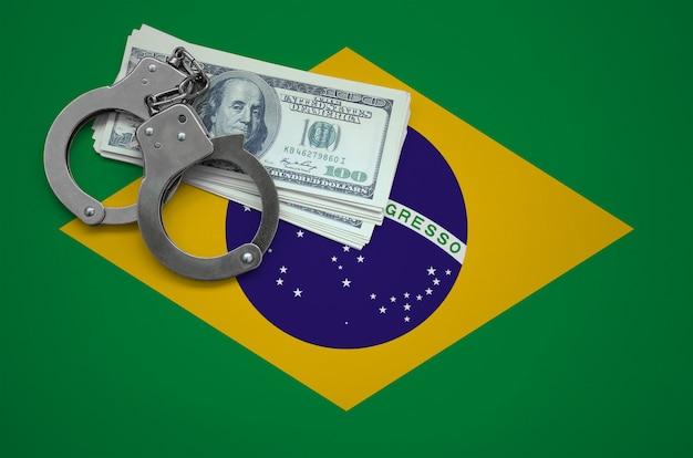 Drapeau du brésil avec des menottes et un paquet de dollars. le concept d'enfreindre la loi et les crimes de voleurs Photo Premium