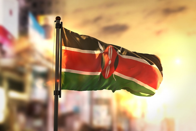 Drapeau du kenya contre la ville contexte flou au sunrise backlight Photo Premium