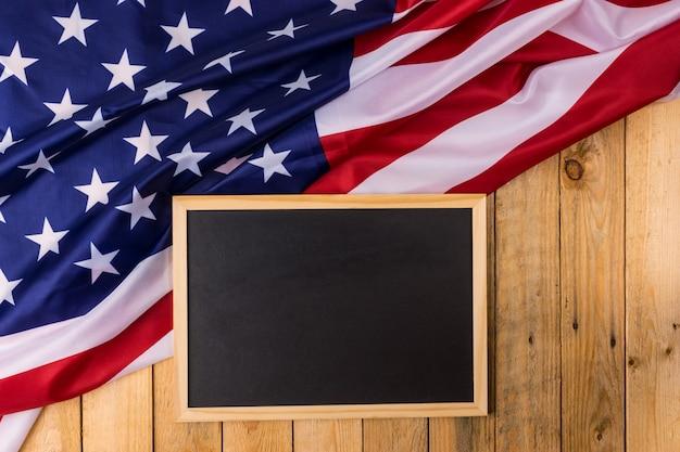 Drapeau des états-unis d'amérique avec tableau sur fond en bois. états-unis: fête des anciens combattants, du mémorial, de l'indépendance et de la fête du travail. Photo Premium