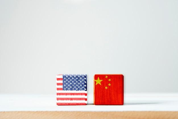 Drapeau des états-unis et drapeau de la chine avec écran d'impression sur cubes en bois. symbole de la barrière fiscale entre les états-unis d'amérique et la chine Photo Premium