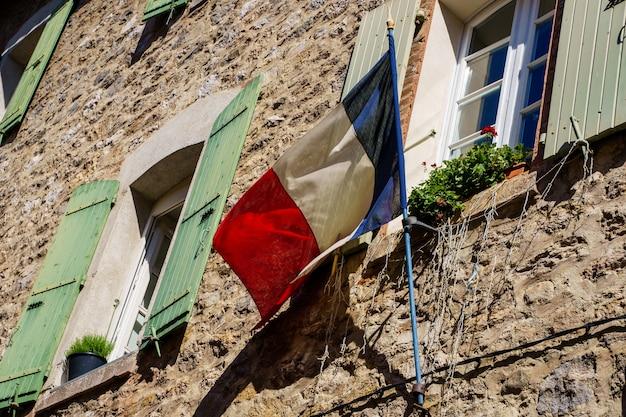 Drapeau Français Cloué Sur Une Façade D'une Vieille Maison En Pierre. Villefranche De Conflent En France Photo Premium