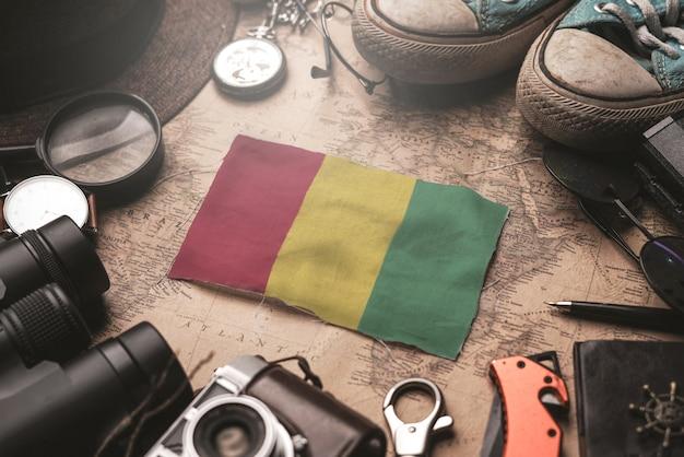 Drapeau De La Guinée Entre Les Accessoires Du Voyageur Sur L'ancienne Carte Vintage. Concept De Destination Touristique. Photo Premium