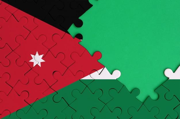 Le drapeau de la jordanie est représenté sur un puzzle complété avec espace de copie vert gratuit sur le côté droit Photo Premium