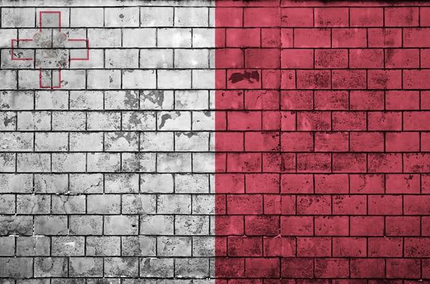 Le drapeau de malte est peint sur un vieux mur de briques Photo Premium