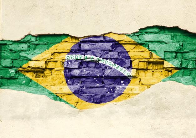 Drapeau National De La Brésil Sur Un Fond De Brique. Mur De Briques Avec Plâtre Partiellement Détruit, Arrière-plan Ou Texture. Photo Premium