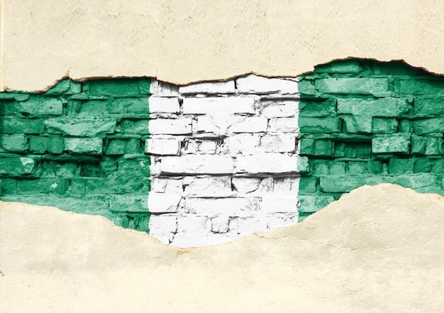 Drapeau National Du Nigéria Sur Un Fond De Brique. Mur De Briques Avec Plâtre Partiellement Détruit, Arrière-plan Ou Texture. Photo Premium