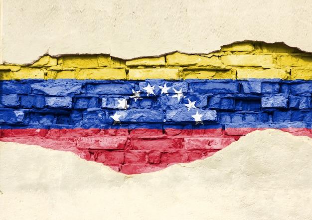 Drapeau National Du Venezuela Sur Un Fond De Brique. Mur De Briques Avec Plâtre Partiellement Détruit, Arrière-plan Ou Texture. Photo Premium