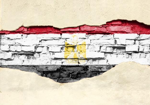 Drapeau National De L'égypte Sur Un Fond De Brique. Mur De Briques Avec Plâtre Partiellement Détruit, Arrière-plan Ou Texture. Photo Premium