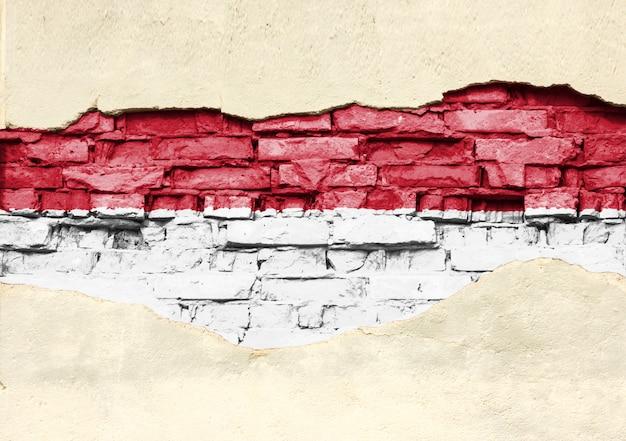 Drapeau National De L'indonésie Sur Un Fond De Brique. Mur De Briques Avec Plâtre Partiellement Détruit, Arrière-plan Ou Texture. Photo Premium