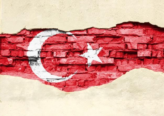 Drapeau National De La Turquie Sur Un Fond De Brique. Mur De Briques Avec Plâtre Partiellement Détruit, Arrière-plan Ou Texture. Photo Premium