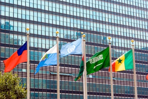Drapeau des nations unies et d'autres pays agitant devant le bâtiment du siège officiel. Photo Premium